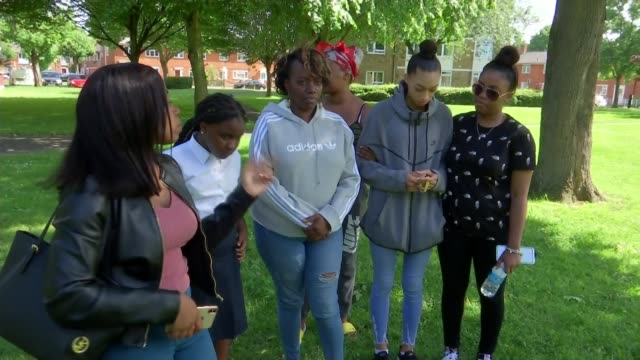 Family of murder victim Cheyon Evans pay tribute ENGLAND London Tooting EXT Maxine Grant Charice Evans and others standing Floral tributes Message on...