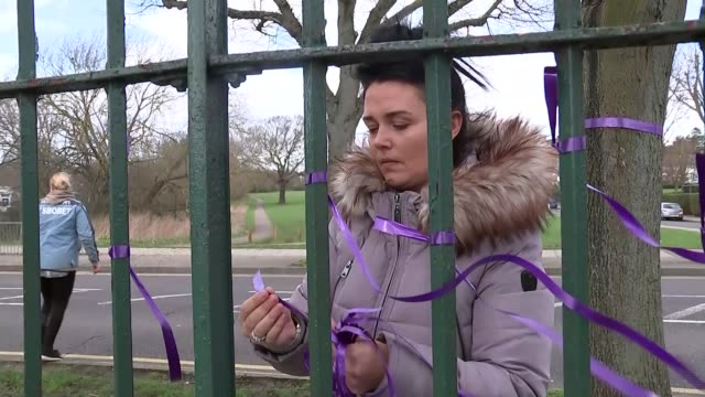 father of murdered teenager jodie chesney makes appeal england london havering romford harold hill ext hands tying purple ribbons to fence woman... - 仮設追悼施設点の映像素材/bロール