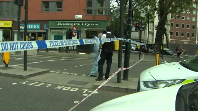 four men stabbed during a fight near chancery lane station england london city of london ext police tape cordon across road with police car in... - itv london tonight weekend点の映像素材/bロール