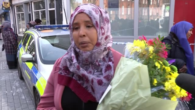 jodie chesney and ayub hassan murders; england: london: west kensington: lanfrey place: ext amina osman delivering flowers to scene where 17-year-old... - 刺傷事件点の映像素材/bロール