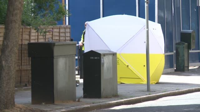 man arrested in connection to stabbing in kennington; england: london: lambeth: kennington: ext police cordon across street forensic tent - ランベス点の映像素材/bロール