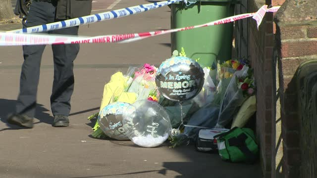 police charge man with walthamstow murder; england: london: walthamstow: ext woman laying flowers at site of stabbing of hussain chaudhry zoom in on... - crime and murder stock-videos und b-roll-filmmaterial