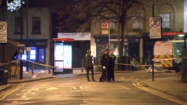 two men stabbed to death and woman shot in 3 separate incidents in capital; england: london: hackney: ext / night general views with police car and... - itv london lunchtime news stock videos & royalty-free footage
