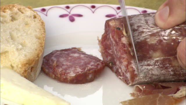 A knife cuts through salami on a plate with sliced bread.