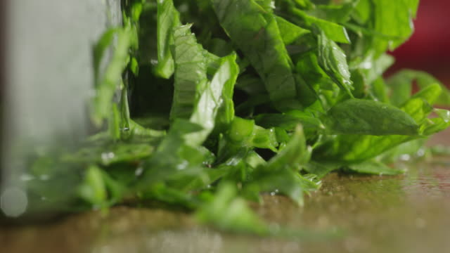Knife cutting basil.