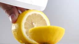 Knife cutting juicy lemon, Close-up slicing lemon on gray background in 4K resolution