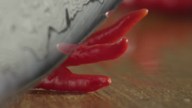 Knife cutting red chilli peppers.