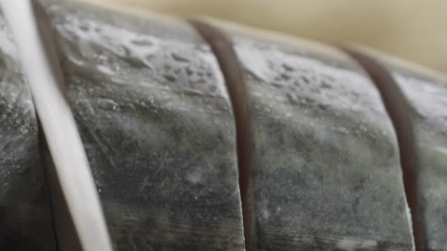 Knife cutting through fish.