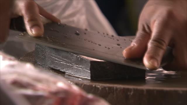 vídeos de stock, filmes e b-roll de knife sharpen on a wet stone - afiado