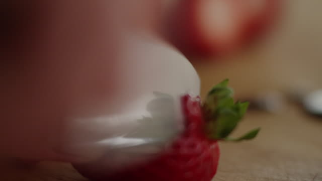 knife slices off top of strawberry and then in half on wooden cutting board - cut video transition stock videos & royalty-free footage