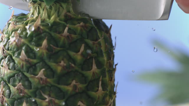 Knife slices through pineapple from top down