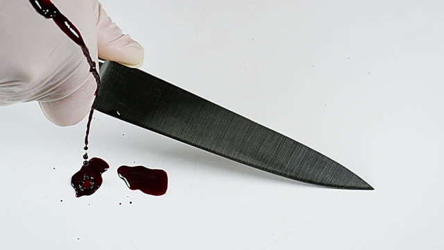 Knife with Blood Dripping on the Blade against White Background, Slow Motion 4K