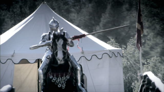 A knight and his horse charge during a joust.
