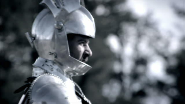 a knight in armor lifts the visor of his helmet near snow-covered trees. - elmetto video stock e b–roll