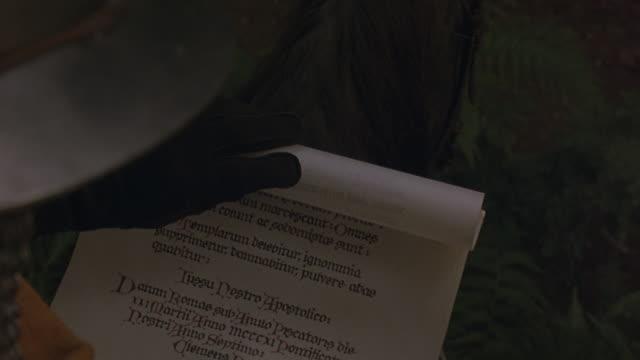 a knight on horseback holds open a scroll written in latin. - lateinische schrift stock-videos und b-roll-filmmaterial