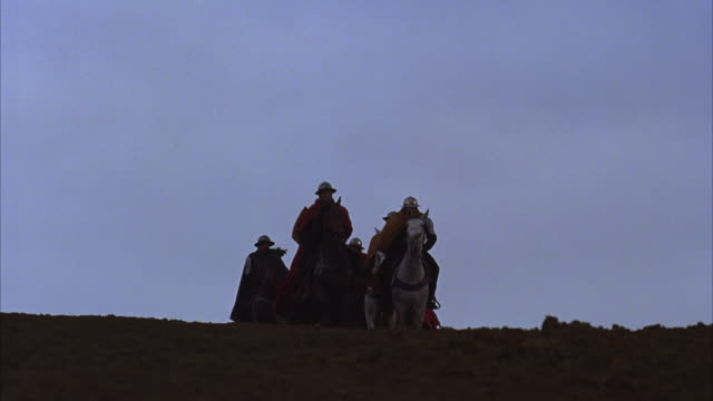 Knights on horseback ride down a hill.