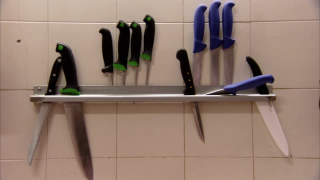 knives hang on the wall of a butcher shop in italy. available in hd. - kitchen knife stock videos & royalty-free footage