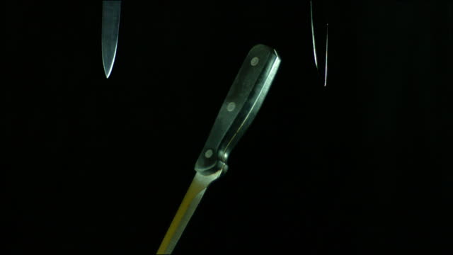 knives rotating and falling to the ground in slow motion against a black background - knife weapon stock videos and b-roll footage