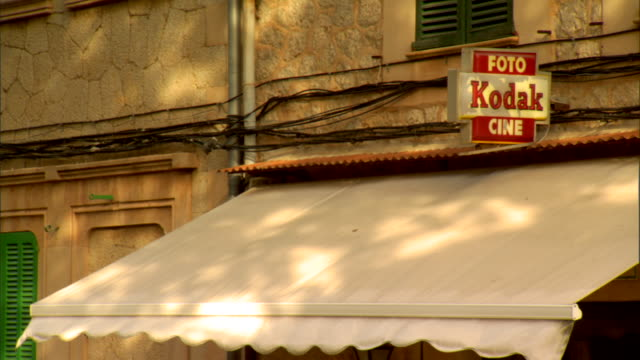kodak foto cine' sign on facade of building over shop awning - awning stock videos & royalty-free footage