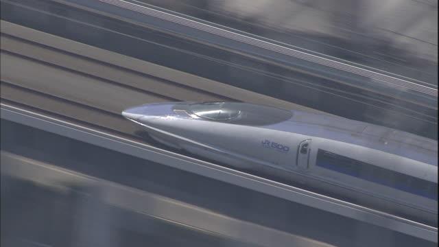 a kodama 500 series train speeds along elevated tracks - shinkansen stock videos & royalty-free footage