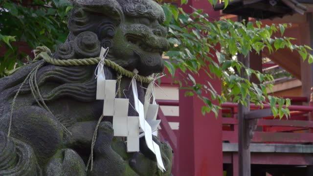 komainu, shinto shrine stone lion-dog, with shide, zigzag-shaped paper streamer, at dobashi hachiman shrine, japan - streamer stock videos & royalty-free footage