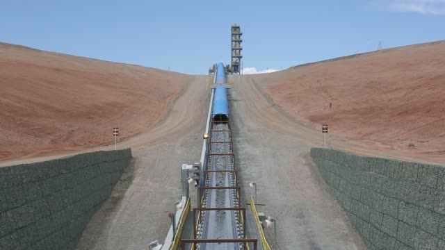 a komatsu ltd dump truck offloads raw ore into the primary crusher at the oyu tolgoi copper gold mine jointly owned by rio tinto groups turquoise... - copper mine stock videos and b-roll footage
