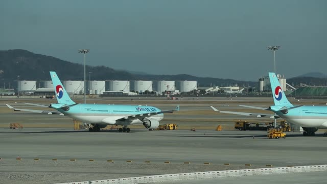 A Korean Air Lines Co aircraft stands on the tarmac outside the nearly completed terminal 2 during a media preview at Incheon International Airport...