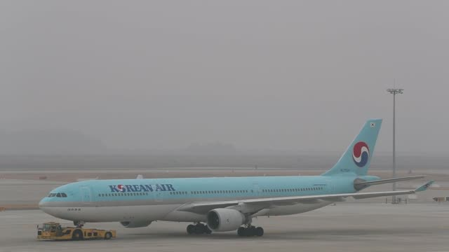 stockvideo's en b-roll-footage met korean air lines co aircrafts stand on the tarmac outside the terminal 2 building at incheon international airport in incheon south korea on thursday... - incheon