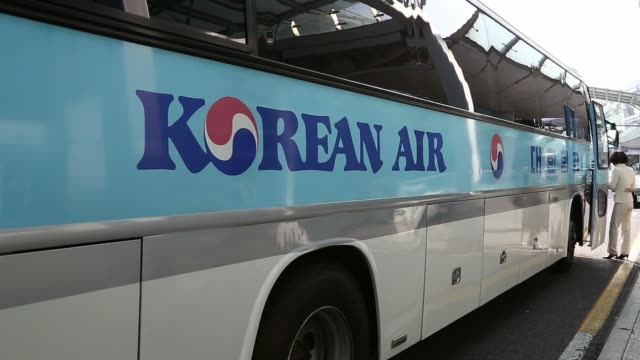 stockvideo's en b-roll-footage met a korean air lines co flight attendant boards a bus and bus pulls away at incheon international airport in incheon south korea on monday jan 27... - incheon
