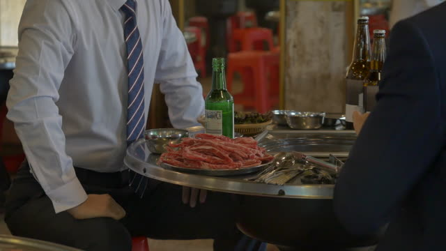 korean barbecue plate and soju (korean alcohol) on a restaurant table - hemd und krawatte stock-videos und b-roll-filmmaterial