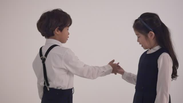 vidéos et rushes de a korean boy and a korean girl doing a pinky promise - doigt humain