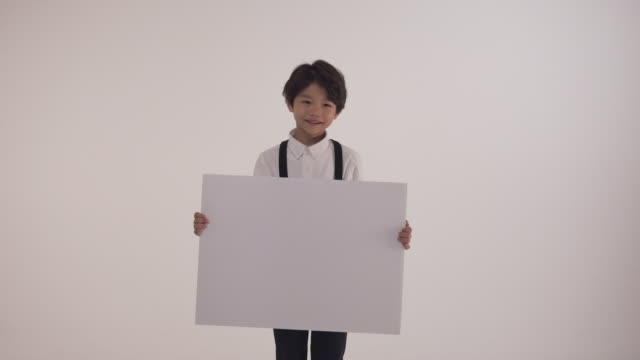 stockvideo's en b-roll-footage met a korean boy holding a blank canvas sign - canvas