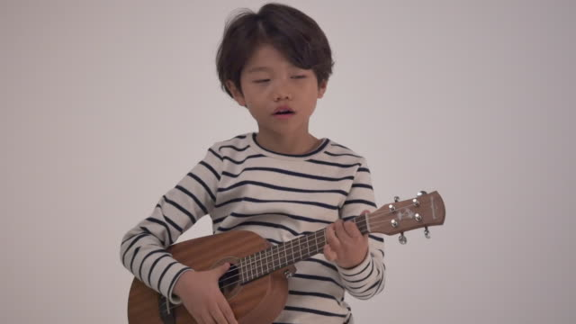vídeos de stock, filmes e b-roll de a korean boy playing the ukulele - extremo oriente