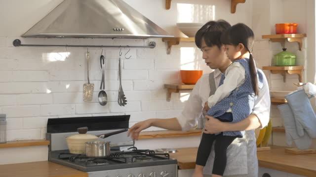 a korean dad and a korean girl at the kitchen - 家事点の映像素材/bロール