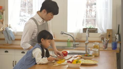 stockvideo's en b-roll-footage met a korean dad and a korean girl cooking - genderblend
