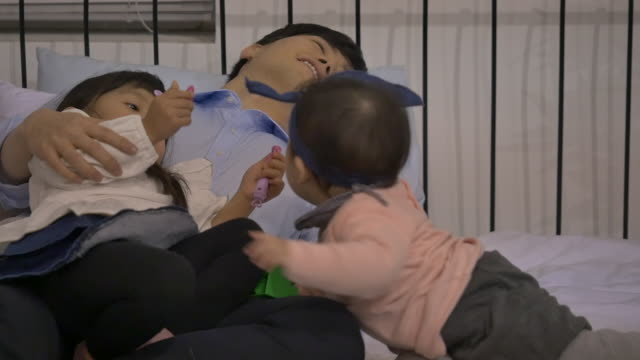 stockvideo's en b-roll-footage met a korean dad and his daughters playing with toys - genderblend
