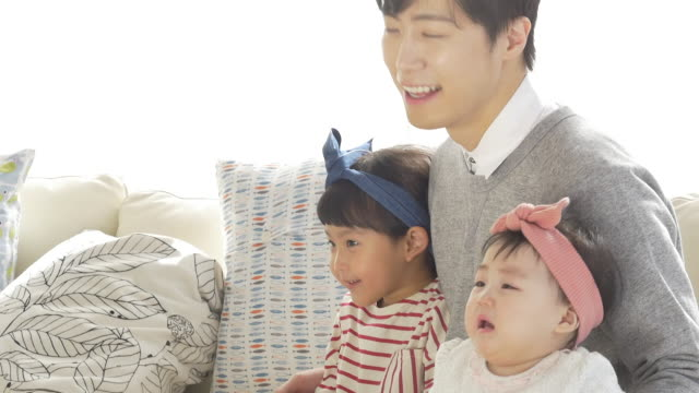 a korean dad and his daughters sitting on a couch - människoarm bildbanksvideor och videomaterial från bakom kulisserna