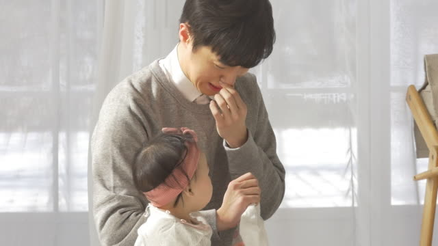 a korean dad frowning at his baby's dirty diaper - おむつ点の映像素材/bロール