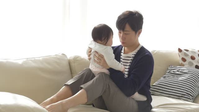vídeos y material grabado en eventos de stock de a korean dad holding a baby on his laps - cojín