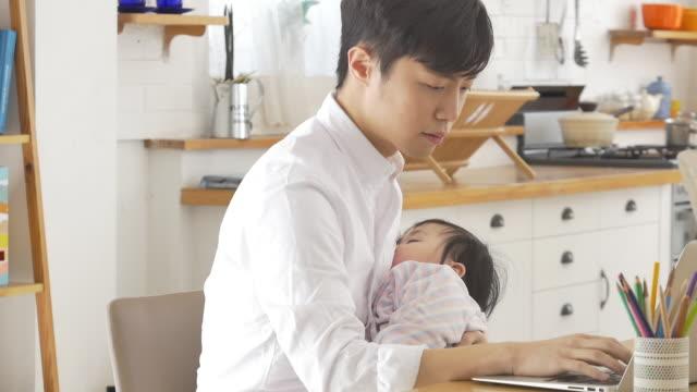 vídeos de stock, filmes e b-roll de a korean dad holding a baby while trying to do his work - braço humano