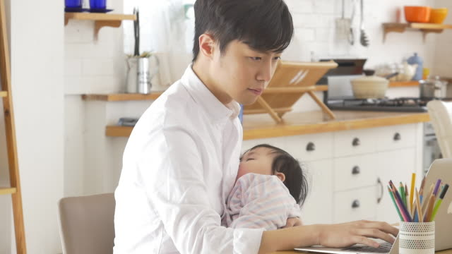 a korean dad holding a baby while trying to do his work - 家事点の映像素材/bロール