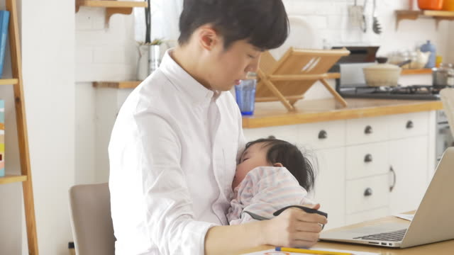 A Korean dad holding a baby while trying to do his work