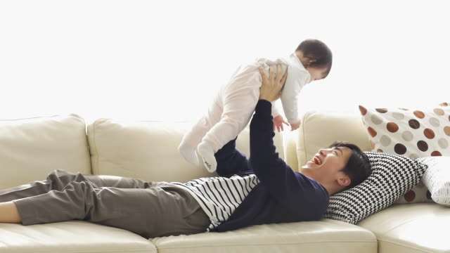 A Korean dad holding his baby in the air while lying down on the couch
