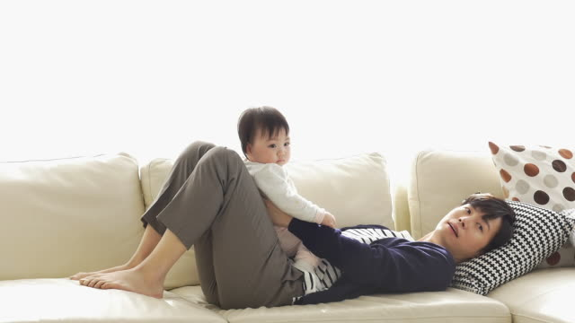 a korean dad holding his baby while lying down on the couch - genderblend stock-videos und b-roll-filmmaterial