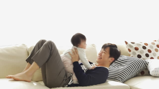 vídeos y material grabado en eventos de stock de a korean dad playing with a baby on the couch - cojín