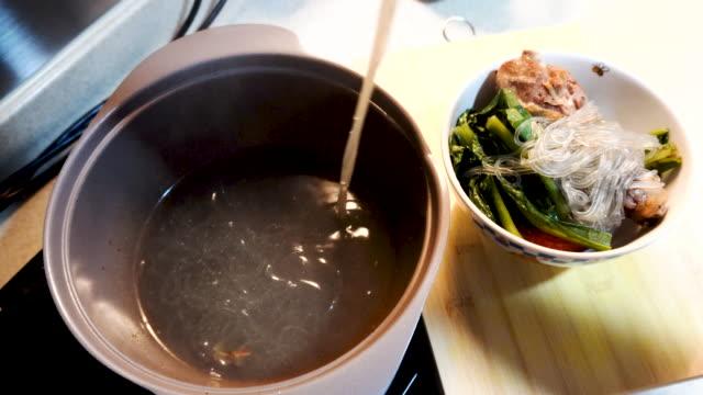 korean food chopsticks take up potato starch noodle to bowl chicken leg tomato vegetable add soup - potato soup stock videos & royalty-free footage