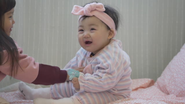 A Korean girl and a baby on the bed