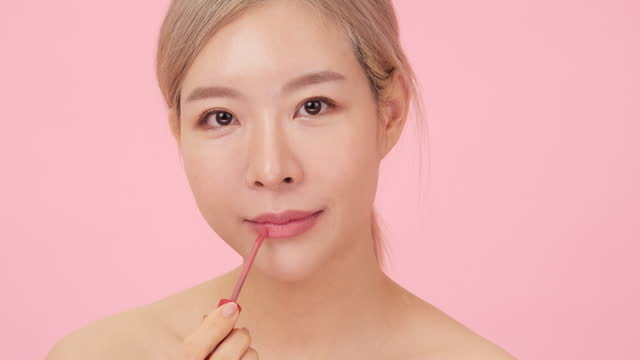 korean girl puts lipstick on her lips. professional makeup. - matte lips stock videos & royalty-free footage