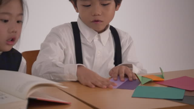 a korean girl studying and a korean boy folding origamis - folding paper stock videos and b-roll footage