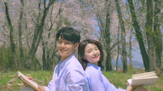 korean man and woman leaning against each other while sitting on the grass field - 年の差カップル点の映像素材/bロール